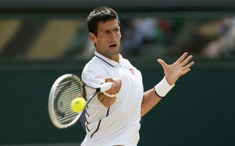 Novak Djokovic of Serbia hits a return to Juan Martin del Potro of Argentina during their men's semi-final tennis match at the Wimbledon Ten