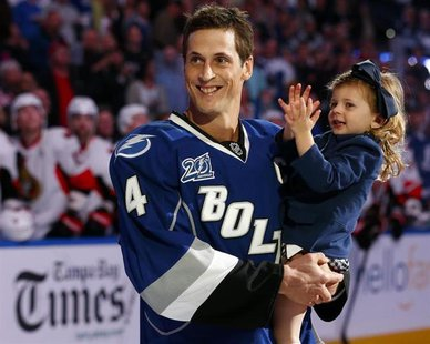 Tampa Bay Lightning's Vincent Lecavalier holds his daughter Victoria during a ceremony honoring his 1000th career NHL game before the team's