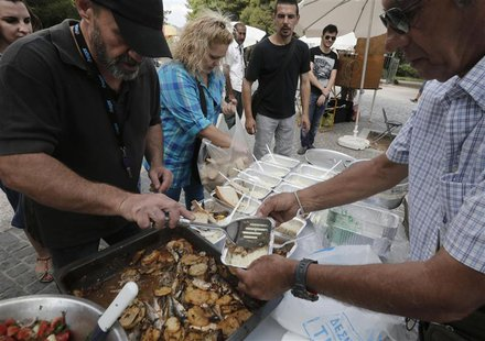 "Constantinos Polychronopoulos (L), from the group called ""O Allos Anthropos"", or ""The Fellow Man"", distributes food portions at a soup kitch"