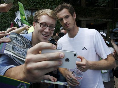 Andy Murray of Britain has a photograph taken by a fan at the Wimbledon Tennis Championships, in London July 6, 2013. REUTERS/Suzanne Plunke