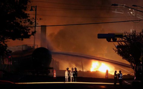 Firefighters look at a train wagon on fire at Lac Megantic, Quebec, July 6, 2013. REUTERS/Mathieu Belanger