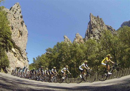 The pack of riders cycles on its way past the Gorges de Saint-Georges during the 195 km eighth stage of the centenary Tour de France cycling