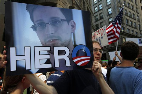 "A demonstrator holds a sign with a photograph of former U.S. spy agency NSA contractor Edward Snowden and the word ""HERO"" during Fourth of J"