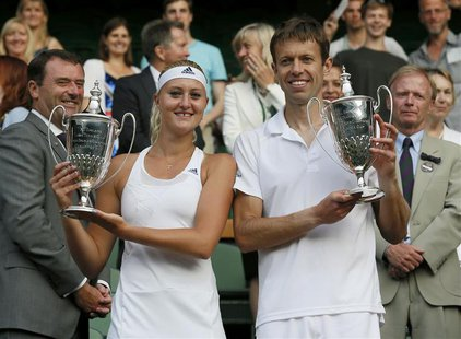 Daniel Nestor (R) of Canada and Kristina Mladenovic of France hold their winners trophies after defeating Bruno Soares of Brazil and Lisa Ra