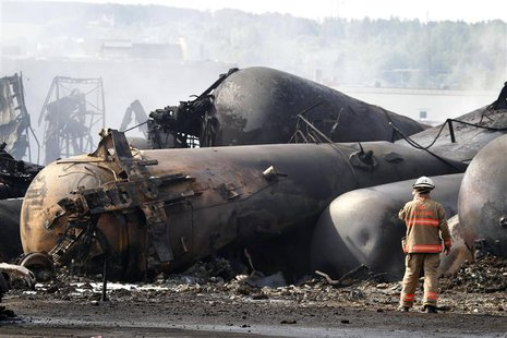 A firefighter works on the scene of a train derailment in Lac Megantic, Quebec, July 7, 2013. REUTERS/Christinne Muschi