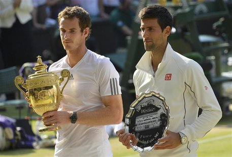 Andy Murray of Britain (L) holds the winners trophy, with Novak Djokovic of Serbia holding the runners-up trophy, after defeating him in the