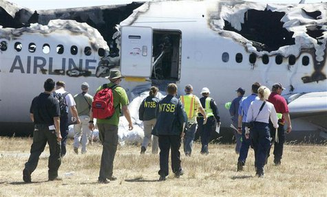 U.S. National Transportation Safety Board (NTSB) investigators work at the scene of the Asiana Airlines Flight 214 crash site at San Francis