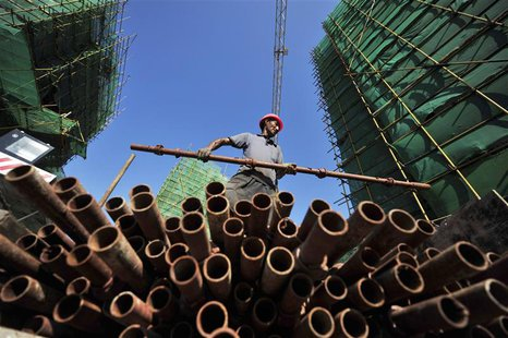 A labourer moves a steel pipe at a residential construction site in Fuzhou, Fujian province July 4, 2013. Picture taken July 4, 2013. REUTER