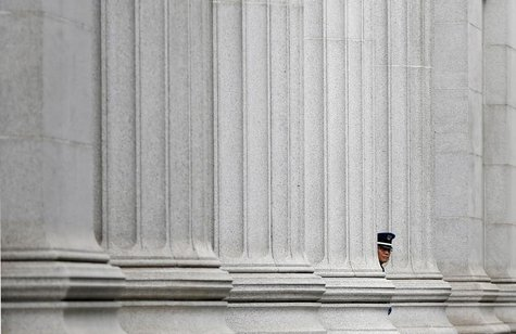 A security guard stands at a bank in front of the Bank of Japan headquarters in Tokyo July 5, 2013. REUTERS/Toru Hanai
