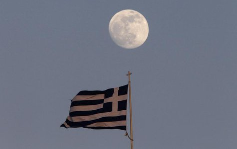 A Greek flag flutters on the top of the parliament as the moon rises in Athens May 23, 2013.. REUTERS/John Kolesidis