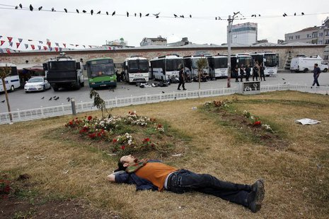 A Gezi Park demonstrator sleeps in front of riot police vehicles at Taksim Square in Istanbul June 14, 2013. REUTERS/Murad Sezer