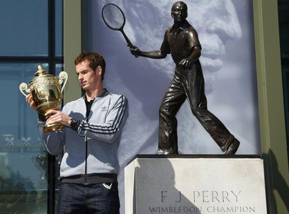 Tennis player Andy Murray of Britain holds the trophy under a statue of former British champion Fred Perry, at Wimbledon, southwest London J