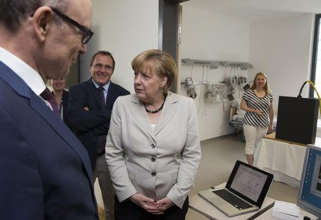 German Chancellor Angela Merkel (3rdL) listens to a presentation of a magnetic tracking system at the newly opened Life Science Campus at Gr