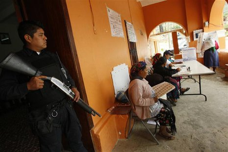 A police officer stands guard at a polling station in San Bartolome Quialana, in the outskirts of Oaxaca, July 7, 2013. REUTERS/Jorge Luis P