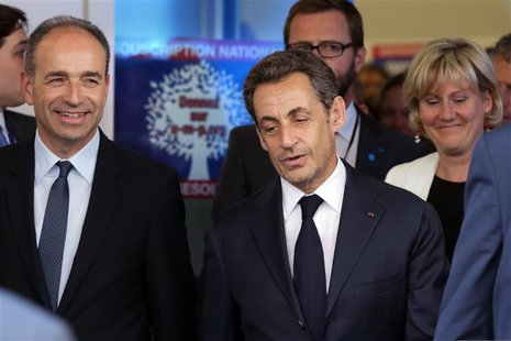 Former French President Nicolas Sarkozy (C), French UMP political party head Jean-Francois Cope (L) and party member Nadine Morano (R) leave