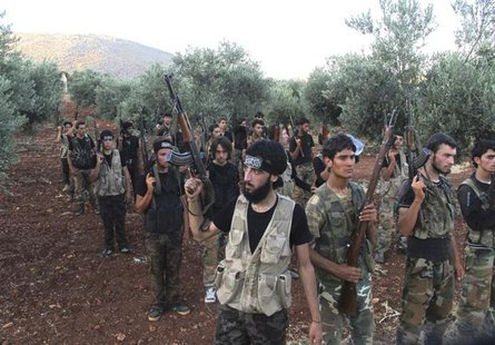 Free Syrian Army fighters, holding their weapons, stand during military training north of Idlib July 7, 2013. Picture taken July 7, 2013. RE