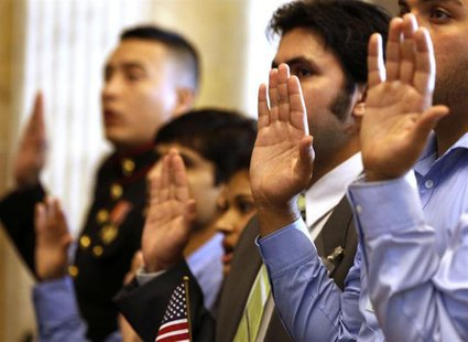 Candidates swear in as United States citizens during a Special Naturalization Ceremony for 30 U.S. citizen candidates in the Cash Room at th