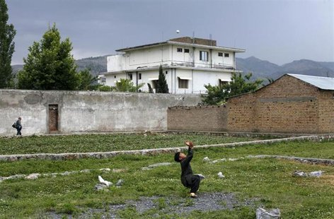 A boy plays with a tennis ball in front of Osama bin Laden's compound in Abbottabad in this May 5, 2011 file picture. REUTERS/Akhtar Soomro/