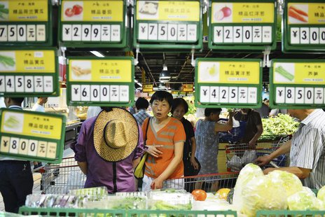 A customer looks at vegetables under price tags at a supermarket in Hangzhou, Zhejiang province July 9, 2013. REUTERS/Stringer