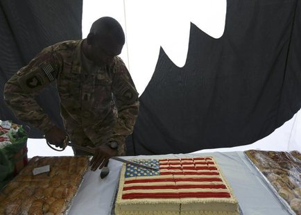 A U.S. soldier cuts into a cake during Fourth of July celebrations at the Bagram airbase, north of Kabul July 4, 2013. REUTERS/Omar Sobhani