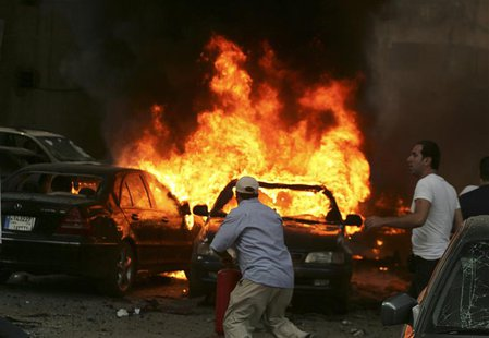 Men try to extinguish fire from burning cars at the site of an explosion, in Beirut's southern suburbs, July 9, 2013. REUTERS/Issam Kobeisy