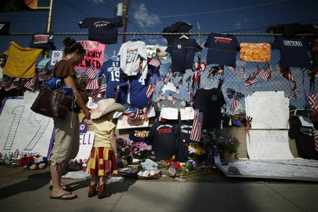 People look at mementos at a memorial dedicated to the 19 firefighters killed in the nearby wildfire in Prescott, Arizona, July 8, 2013. REU