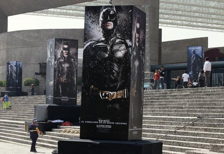 "Posters of the film ""The Dark Knight Rises"" are displayed outside as people wait for the midnight premiere of the final instalment of Christ"