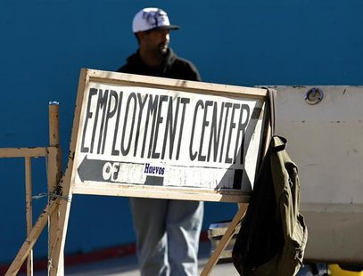A day labourer stands behind a sign for an employment center in San Diego, January 6, 2011. REUTERS/Mike Blake