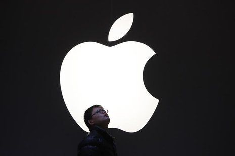 A man stands in front of an Apple logo in downtown Shanghai February 18, 2012. REUTERS/Aly Song