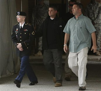 U.S. Army Private First Class Bradley Manning (L) is escorted out after a day of testimony at his court martial trial at Fort Meade, Marylan