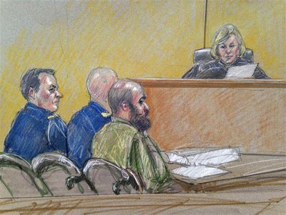 U.S. Army Major Nidal Hasan (C), accused of killing 13 soldiers in a 2009 Fort Hood shooting rampage, is seen in a courtroom sketch as he si