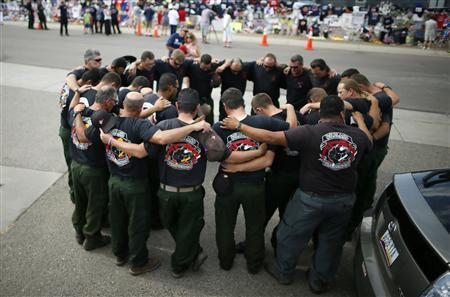 Firefighters pray in front of a memorial dedicated to the 19 firefighters killed in the nearby wildfire in Prescott, Arizona, July 8, 2013.  REUTERS/Lucy Nicholson