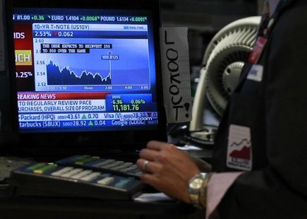 A trader works on the floor of the New York Stock Exchange as The Federal Reserve rate announcement is shown on a screen, November 3, 2010.
