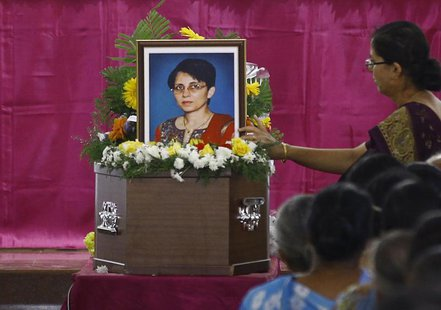 A woman puts flowers on Jacintha Saldanha's coffin during her funeral inside a church in Shirva, about 52 km (32 miles) north of Mangalore D