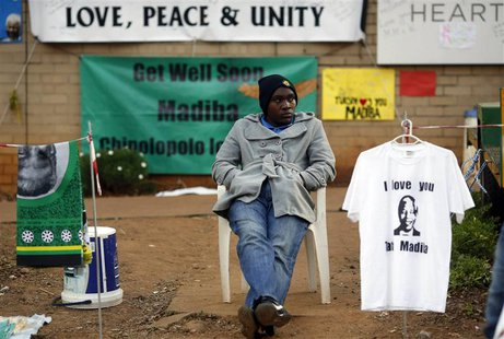 A street vendor sells t-shirts and fabric outside the hospital where ailing former President Nelson Mandela is being treated in Pretoria, Ju