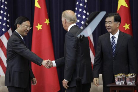 U.S. Vice President Joe Biden (C) shakes hands with Chinese State Councilor Yang Jiechi as Chinese Vice Premier Wang Yang (R) look on during
