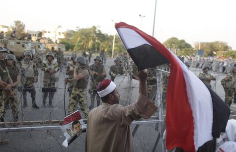 A supporter of ousted Egyptian President Mohamed Mursi waves an Egyptian flag in front of security personnel outside of the Republican Guard