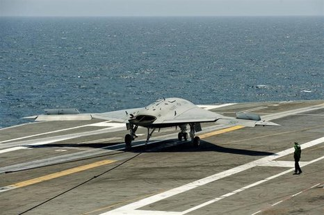 An X-47B pilot-less drone combat aircraft comes to a stop after landing on the deck of the USS George H.W. Bush aircraft carrier in the Atla