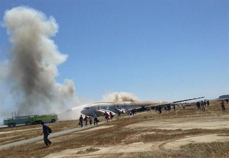 Passengers evacuate from Asiana Airlines Boeing 777 aircraft after a crash landing at San Francisco International Airport in San Francisco,