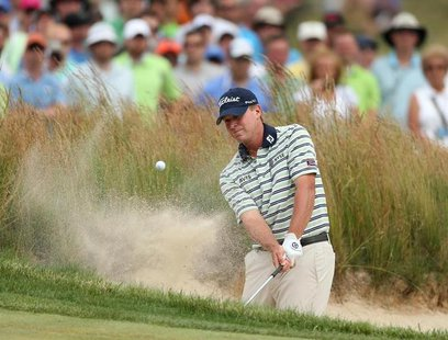 Steve Stricker of the U.S. hits from a bunker on the fourth hole during the final round of the 2013 U.S. Open golf championship at the Merio