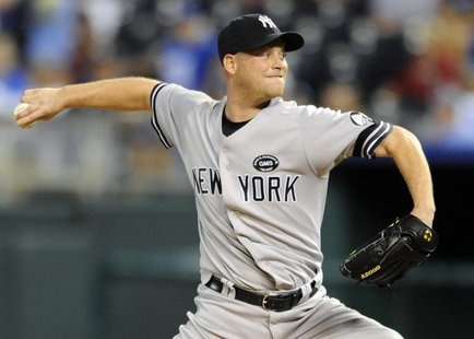 New York Yankees relief pitcher Chad Gaudin delivers a sixth inning pitch against the Kansas City Royals during their rain-delayed MLB Ameri
