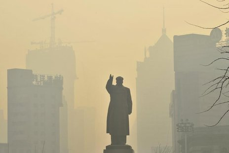 A statue of China's late Chairman Mao Zedong is seen in front of buildings during a hazy day in Shenyang, Liaoning province, May 7, 2013. RE