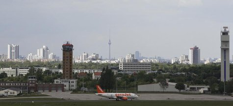 An aircraft operated by easyJet sits on tarmac with the skyline of German capital of Berlin in the background at Schoenefeld airport, May 17