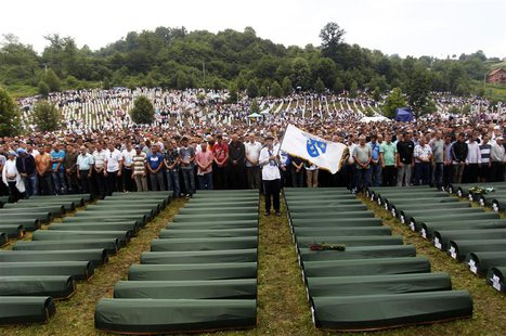 Bosnians pray in front of 409 coffins of newly identified victims of the 1995 Srebrenica massacre in the Potocari Memorial Center, near Sreb