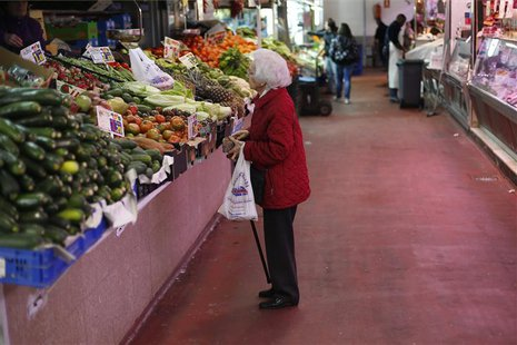 A woman looks at fruits and vegetables at a market stall in Madrid January 29, 2013. REUTERS/Juan Medina