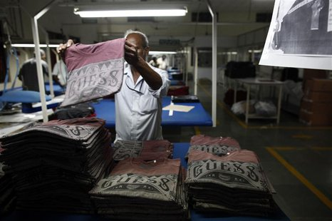 An employee sorts newly finished T-shirts at the Estee garment factory in Tirupur in the southern Indian state of Tamil Nadu June 19, 2013.