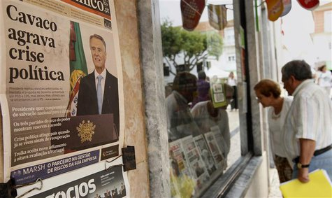 People look at the front pages of newspapers displayed behind the window of a shop in Ericeira village, 40 km (24 miles) north of Lisbon Jul
