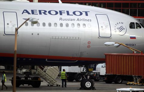 Airport staff walk under Aeroflot's Moscow-Havana flight aircraft at Havana's Jose Marti International Airport July 11, 2013. REUTERS/Desmon