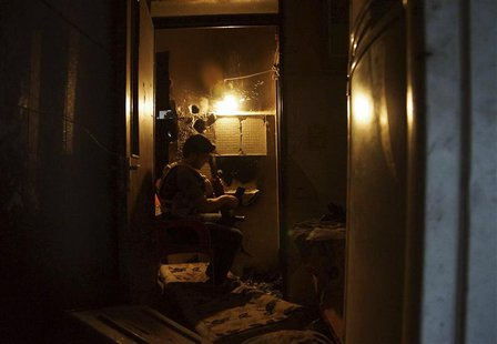 A Free Syrian Army fighter inspects his weapon inside a house in Deir al-Zor July 11, 2013. Picture taken July 11, 2013. REUTERS/Khalil Asha