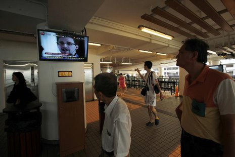 Passengers watch news footage of Edward Snowden before getting aboard a Star Ferry to cross Hong Kong's Victoria Harbour July 12, 2013. REUT